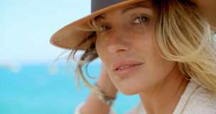Blond Woman Wearing Hat in front of Blue Ocean stock footage