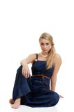 Blond woman wearing jeans sitting Royalty Free Stock Image