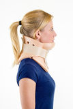 Blond Woman Wearing Neck Brace in Studio. Close Up Side Profile of Young Blond Woman with Hair in Ponytail in Blue T-Shirt and Wearing Neck Brace in Studio with Royalty Free Stock Photo