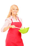 Blond woman wearing red apron and holding kitchen utensil Royalty Free Stock Photography