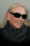 Blond woman wearing scarf and sunglasses smiling Stock Photography