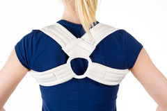 Blond Woman Wearing Supportive Back Brace. Close Up Rear View of Blond Woman in Blue T-Shirt Wearing Supportive Orthopedic Back and Shoulder Brace in Studio with Royalty Free Stock Images