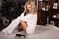 Blond woman wears cozy knitted cardigan,posing beside Christmas tree Stock Image