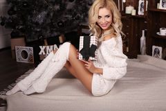 Blond woman wears cozy knitted cardigan,posing beside Christmas tree Royalty Free Stock Photography