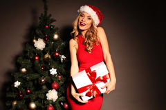 Blond woman wears Santa hat posing with presents, beside Christmas tree Stock Images