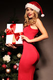 Blond woman wears Santa hat posing with presents, beside Christmas tree Stock Photos