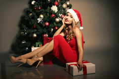 Blond woman wears Santa hat posing with presents, beside Christmas tree Stock Photo