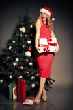 Blond woman wears Santa hat posing with presents, beside Christmas tree Royalty Free Stock Images