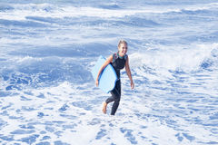 Blond woman in wetsuit and swimming board in the water Stock Photo