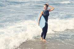 Blond woman in wetsuit walking out of the water. Beautiful blond woman in wetsuit with swimming board walking out of the water Stock Images