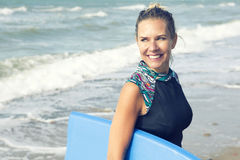 Blond woman in wetsuit walking out of the water Stock Photo