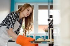 Blond woman in a white apron bakes bread rolls Stock Images