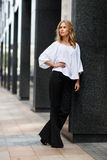 Blond woman in white blouse and black trousers near building. Thoughtful blonde woman in white blouse and black trousers in street near the building stock photo