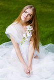 Blond woman in white dress with orchid Royalty Free Stock Images