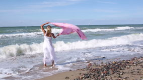 Blond woman in white dress walking on the beach with shawl in the wind stock video footage