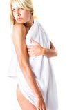 Blond Woman In White Towel. Beautiful young blond-haired, blue-eyed woman, wrapped in a white towel.  Serious expression.  Isolated on white background Royalty Free Stock Images
