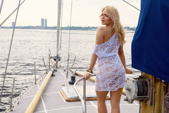 Blond woman in white transparent dress standing on yacht. Young beautiful blond woman in white transparent dress standing on yacht at sunny day Stock Photography