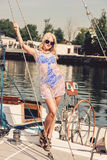 Blond woman in white transparent dress and swimsuit standing on yacht. Young beautiful blond woman in white transparent dress and swimsuit standing on yacht at Royalty Free Stock Images