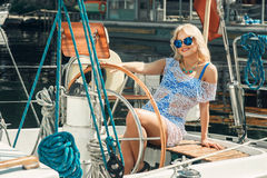 Blond woman in white transparent dress and swimsuit standing on yacht. Young beautiful blond woman in white transparent dress and swimsuit standing on yacht at Stock Photography