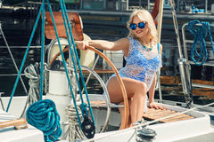 Blond woman in white transparent dress and swimsuit standing on yacht. Young beautiful blond woman in white transparent dress and swimsuit standing on yacht at Royalty Free Stock Photography