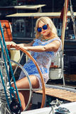Blond woman in white transparent dress and swimsuit standing on yacht Royalty Free Stock Photography