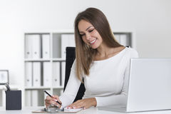 Blond woman in white writing in clipboard Stock Photo