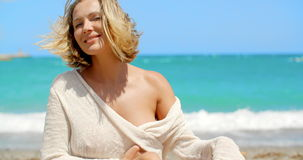 Blond Woman with Wind Swept Hair Sitting on Beach stock video
