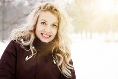 Blond woman in winter landscape with sun flare. Blond woman in snow covered winter landscape with sun flare light leak Royalty Free Stock Images