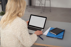 Blond woman working on a laptop computer stock images