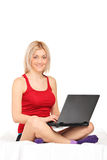 Blond woman working on a laptop seated on towel Royalty Free Stock Photo