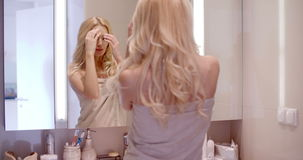 Blond Woman Wrapped in Towel In Front a Mirror stock footage
