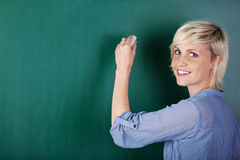 Blond Woman Writing On Chalkboard Royalty Free Stock Photos