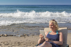 Blond Women Using Tablet At The Beach Stock Photo