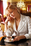 Blond women in Whit suit drinks tee Stock Photo