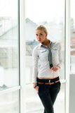 Blond young beautiful business woman standing relaxed near window at her office Stock Photos