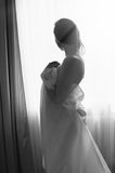 Blond young beautiful woman having fun hiding. Black and white portrait of young beautiful lady hiding under white sheet standing on light window copy space Royalty Free Stock Photo
