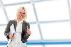 Blond young business woman with a clipboard. Smiling blond young business woman with a clipboard and thumb up Stock Photos