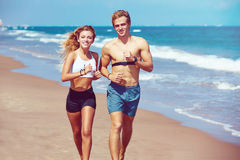 Blond young couple running on a beach in summer. Blond young couple running on the beach in summer vacation Stock Photo