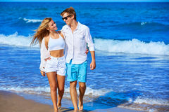 Blond young couple walking in the beach shore Royalty Free Stock Image