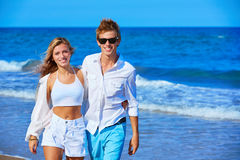 Blond young couple walking in the beach shore Royalty Free Stock Photography