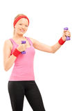 Blond young female in sportswear exercising with barbells Royalty Free Stock Photo