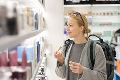 Blond young female traveler wearing travel backpack choosing perfume in airport duty free store. royalty free stock images
