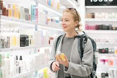 Blond young female traveler wearing travel backpack choosing perfume in airport duty free store. royalty free stock image