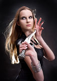 Blond young girl holding dagger. Blond young girl holding old dagger royalty free stock image