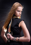 Blond young girl holding dagger. Blond young girl holding old dagger royalty free stock photography