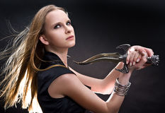 Blond young girl holding dagger Stock Photo