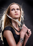 Blond young girl holding dagger. Blond young girl holding old dagger stock photography