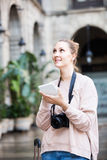 Blond young girl holding tablet in hands and looking up her way Stock Photography