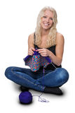 Blond young girl knitting. A young pretty girl with blond hair, knitting, isolated on white background Royalty Free Stock Image