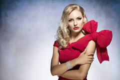 Blond young girl in red with big bow. Young and beautiful blond woman in red dress with nice hair style and a big bow on shoulder.looking in camera stock photos